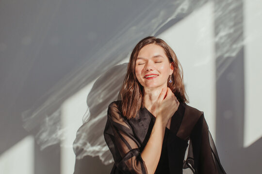 Portrait of a happy beautiful woman with her hand on her neck
