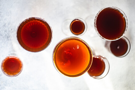 Overhead view of assorted glasses filled with red wine on a table