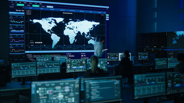 Project Manager Uses Digital Tablet Looks at Big Screen Display Showing Infographics and Global World Map Data. Telecommunications Control Monitoring Room with People Working