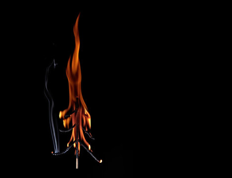 Burning Christmas tree made of matches on black background