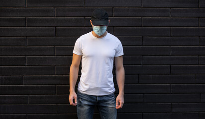 Unrecognizable man in white empty t-shirt standing against a brick wall, mockup template, covid-19...