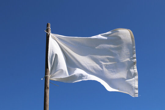 The white flag against the blue sky.  Surrender concept.