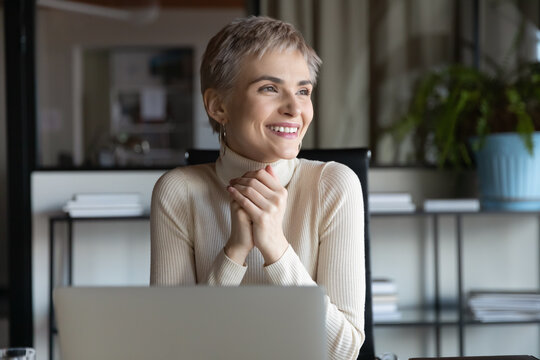 Smiling young female employee work online on laptop in office look in distance think plan. Happy millennial Caucasian businesswoman use computer visualize career success. Business vision concept.