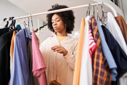 Woman looking through the hangers with clothes ready for alteration