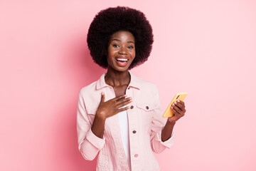 Obraz Portrait of charming cheerful girl using device app 5g post smm enjoying free time isolated over pink color background - fototapety do salonu