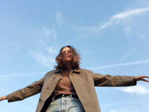 Low Angle View Of Smiling Young Woman Looking Away Against Sky