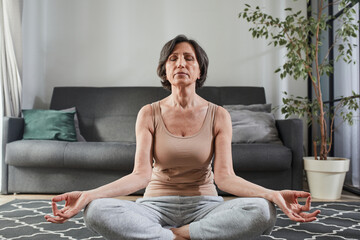 Senior woman in casual clothes meditating and sitting on lotus pose at home