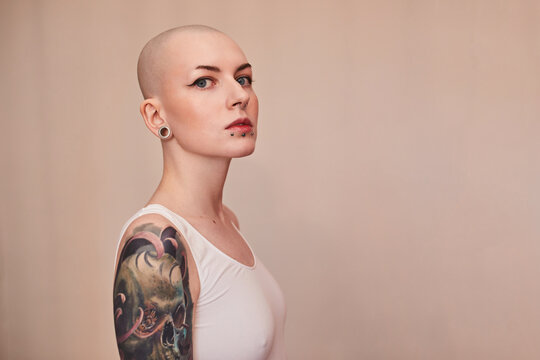 Bald masculine woman posing fashionably with serious emotions