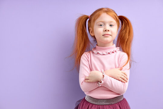 Emotional portrait of ittle beautiful girl with crossed arms isolated on purple background, offended on something