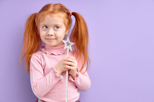 smiling little girl child holding magic wand in hand, want to be enchantress, adorable cute kid girl with natural red hair dreams looking away, game of fairy. Costume party