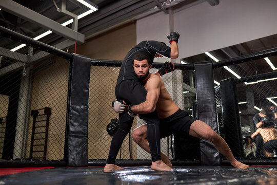 Athlete MMA boxers fighters fight in fights without rules in ring octagons. Mixed martial artists during fight. sport and boxing concept