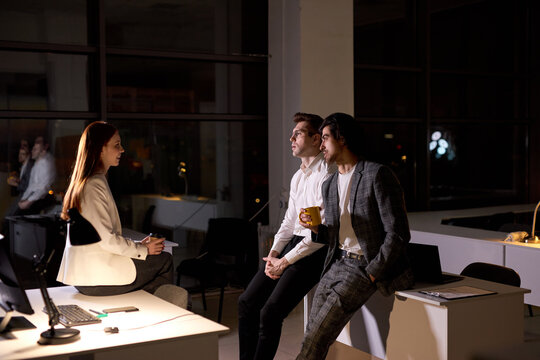 Colleagues in formal outfit stand having conversation, taking a break at late night in boardroom, smiling, discussing, sharing ideas, explaining plans. teamworking, office workers concept
