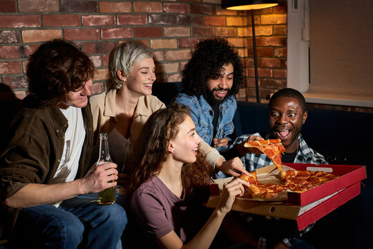 young people eating pizza and watching tv.Home party.Fast food concept. Americans spending free time together in the evening