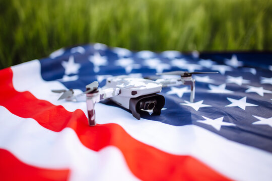 A closeup shot of a lying drone. The drone lies on the American flag against the background of a green field of wheat. Independence Day. 4th of July. Technologies, innovation.
