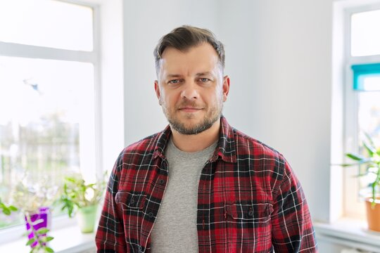 Portrait of 40 years old man, smiling male in plaid casual shirt looking at camera