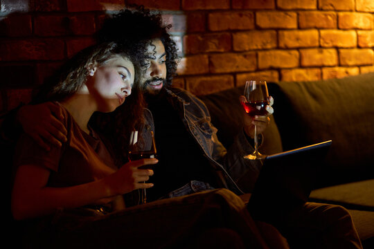Lovely Interracial Couple Spend Weekends Together Watching Movie On Laptop At Home, Drinking Red Wine. Attractive Man And Woman Having Romantic Time, In Domestic Casual Wear