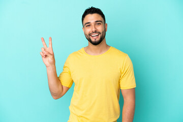 Obraz Young arab man isolated on blue background smiling and showing victory sign - fototapety do salonu