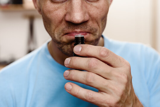 Young ill man trying to sense smell of tube essential oil
