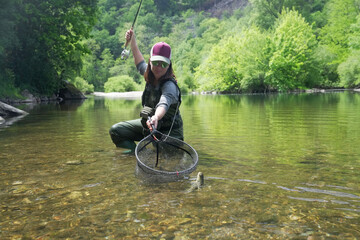 Obraz young woman fly fishing and catching a brown trout - fototapety do salonu