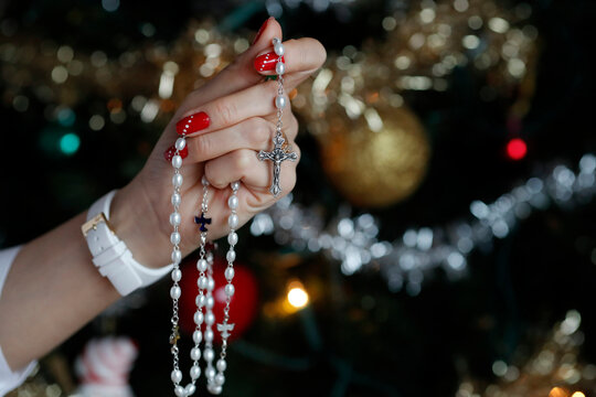 Woman praying the rosary with Christmas tree in background.  Close-up on hand.  France.