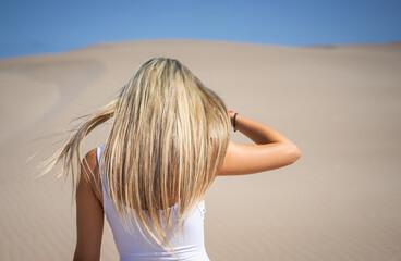 Fototapeta Chica rubia de pelo largo caminando sobre la arena de un desierto con un vestido blanco en un dia con mucho viento y soleado  obraz