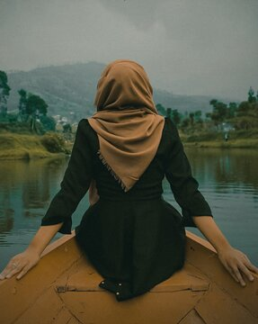 Rear View Of Woman Sitting On Rowboat In Lake