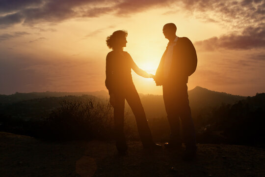 Senior couple in love together outdoor in mountains over scenic sunset sun sky background.