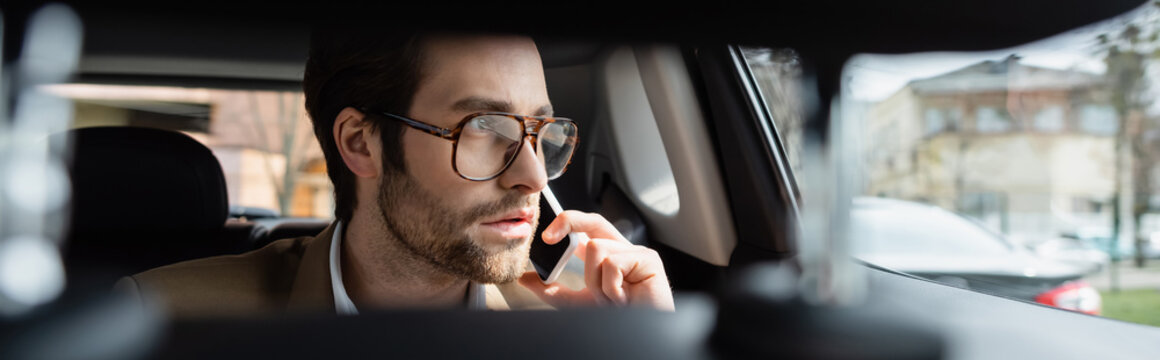 man in glasses talking on smartphone in car, banner