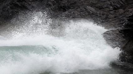 Zbliżenie fali rozbijającej się o skały