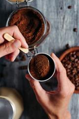 Fototapeta man fills with coffee the funnel of a moka pot obraz