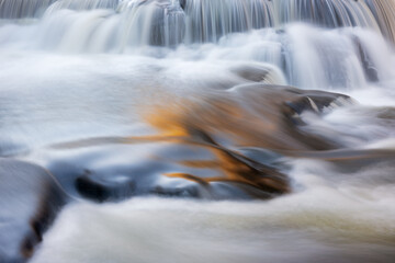 Autumn landscape of cascades at Bond Falls, captured with motion blur, and illuminated by reflected color from sunlit autumn foliage and blue sky overhead, Michigan's Upper Peninsula, USA Wall mural