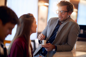 young handsome man drinking coffee, leaned on a bar, talking to attractive female sitting - fototapety na wymiar