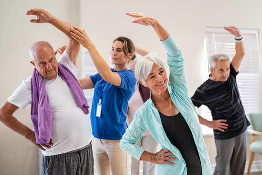 Senior people stretching with trainer at retirement community