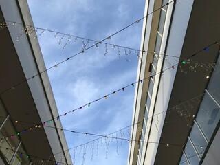 Fototapeta premium 建物の間にデコレーションされたカラフルな電飾、快晴