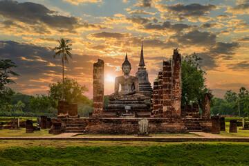 Obraz Buddha statue and pagoda Wat Mahathat temple with dramatic syk sunset, Sukhothai Historical Park, Thailand - fototapety do salonu