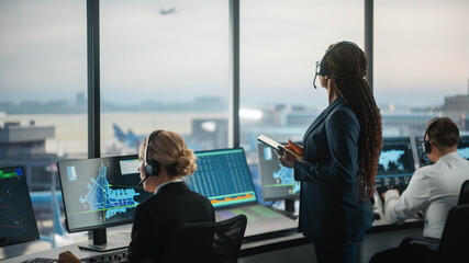 Fototapeta Black Female Air Traffic Controller Holding Tablet in Airport Tower. Office Room is Full of Desktop Computer Displays with Navigation Screens, Airplane Departure and Arrival Data for the Team. obraz