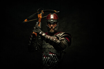 Obraz Portrait of a medieval fighter holding a crossbow in his hands - fototapety do salonu