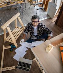 Fototapeta Asian artisan with laptop making lumber furniture obraz