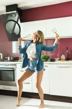 Attractive woman dancing and singing  on the kitchen while cooking during sunny morning