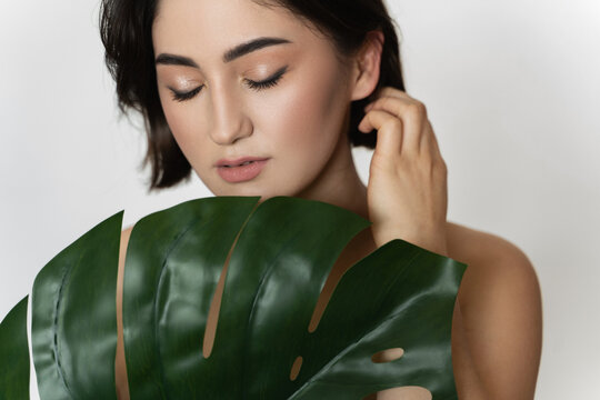 Beautiful woman with a smooth skin holding green tropical leaf on white background