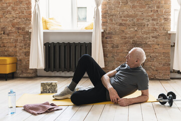 Elderly man relaxing after his fitness workout at home