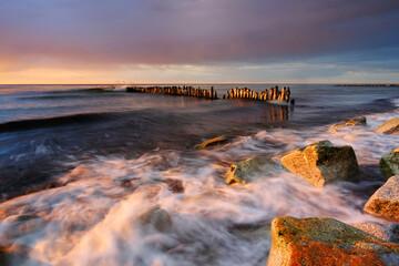 Fototapeta Morze Bałtyckie, kamieniste wybrzeże , falochron ,zachód słońca, Kołobrzeg, Polska. obraz