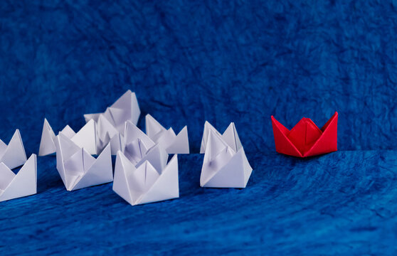 Leadership concept shown using white paper boats wandering in the sea and one red boat on track.