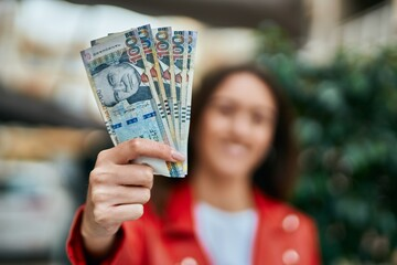 Obraz Young hispanic woman smiling happy holding peruvian sol banknotes at the city. - fototapety do salonu