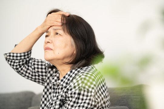 頭痛を感じて頭を抑えるシニア女性2 コピースペースあり ズーム
