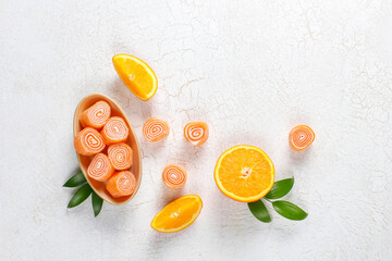 Orange color jelly rolls with orange fruits.
