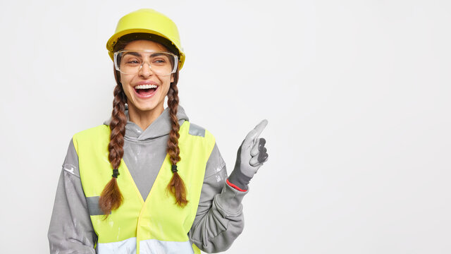 Positive woman builder on construction site demonstrates something over blank space wears hard hat protective glasses uniform has engineering career isolated over white background. Safety apparel