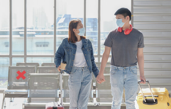 Asian young couple traveler wearing face mask, holding hands together and making eye contact during walk with luggage at public terminal station. New normal lifestyle concept.