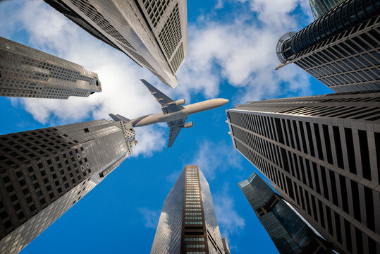 A low-angle view of Passenger planes flying past numerous commercial buildings and skyscrapers in the city center