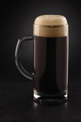 Obraz Stein with fresh stout beer with cap of foam on a black. - fototapety do salonu